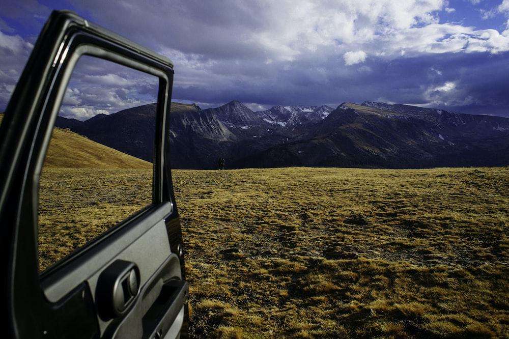 opened vehicle door with mountain alps view