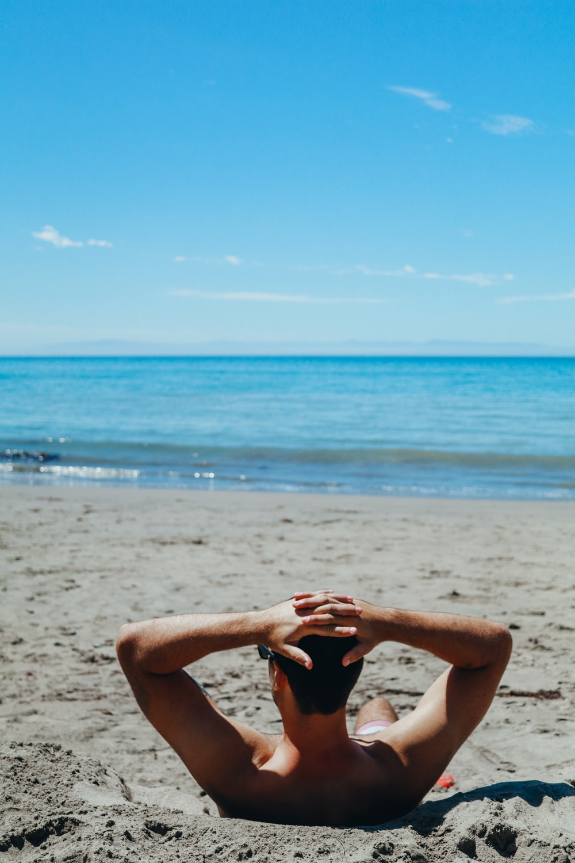 man leaning on beach