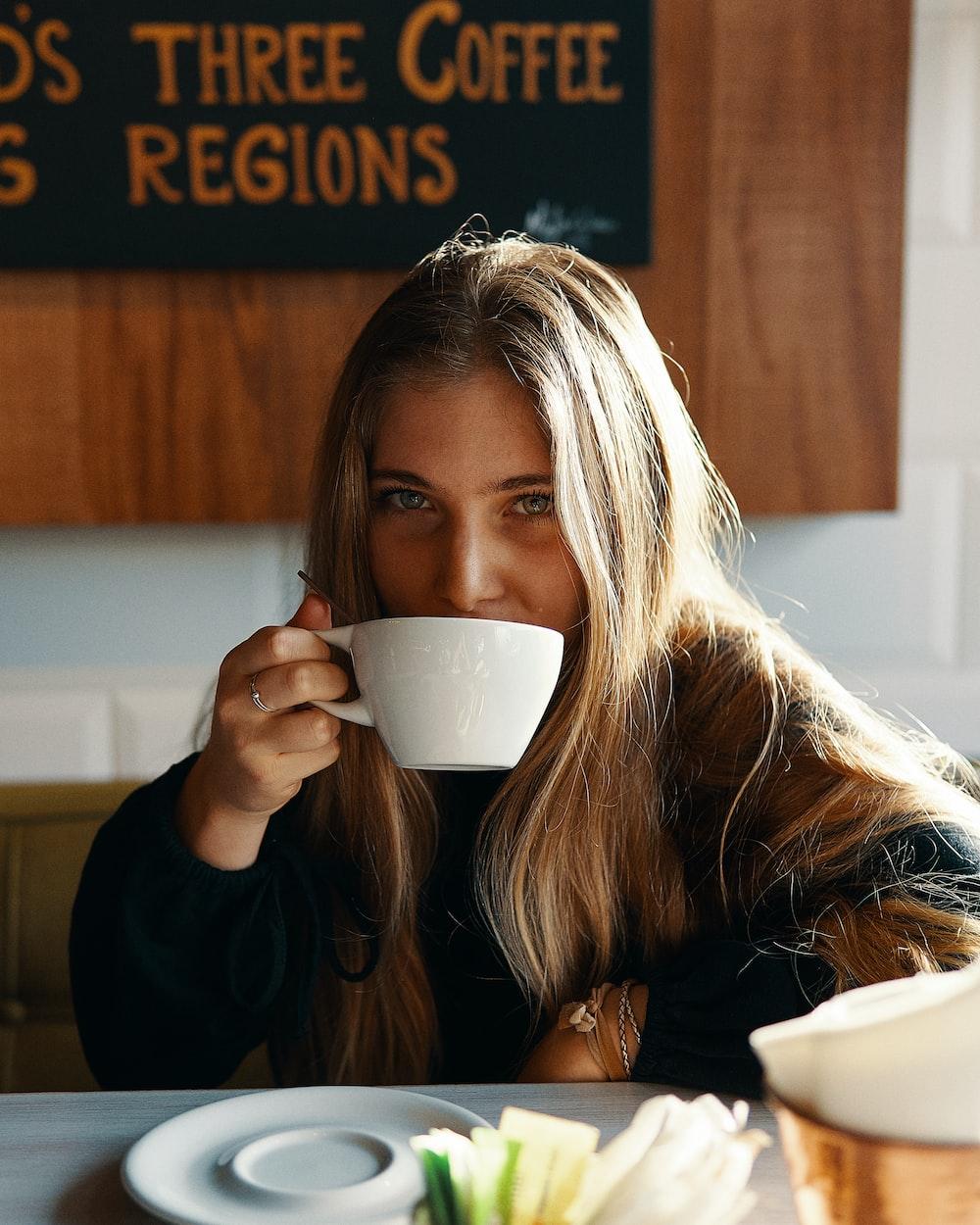 woman holding white ceramic teacup