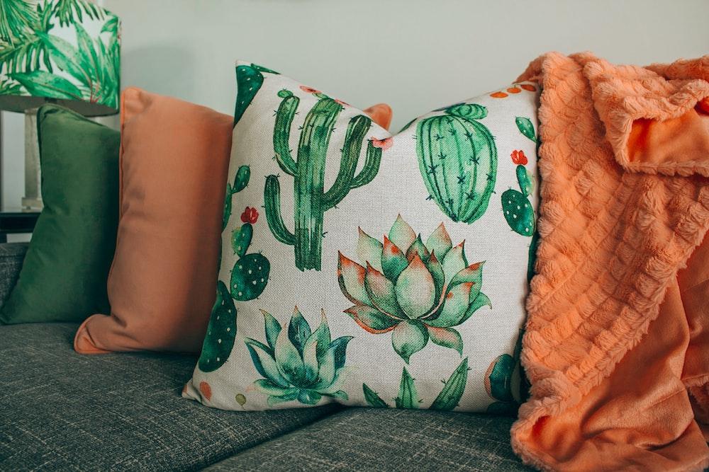 three green, orange, and white throw pillows on sofa