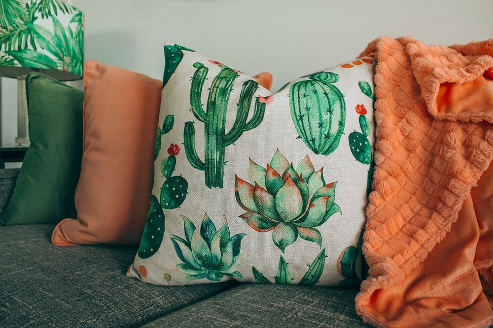 three green, orange, and white throw pillows on sofa
