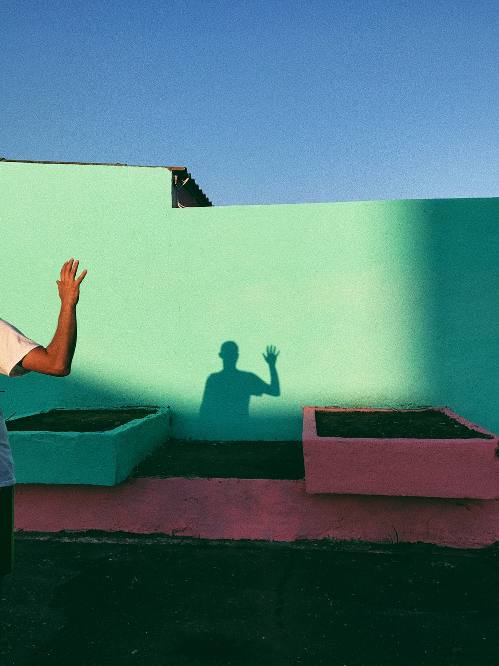 person waving reflecting shadow on teal wall paint