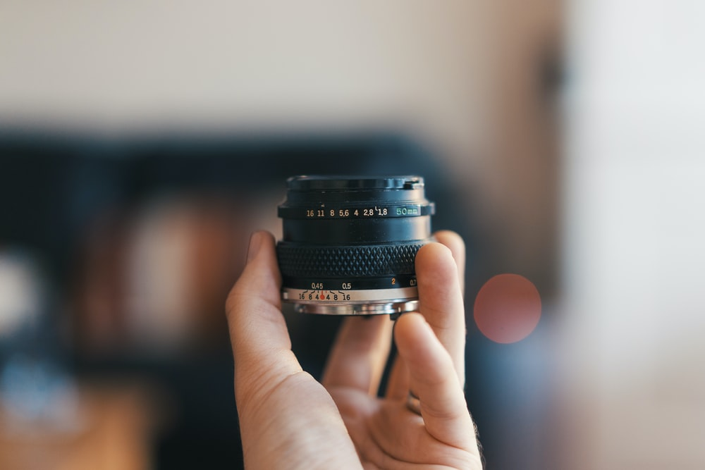selective focus photography of person holding camera lens