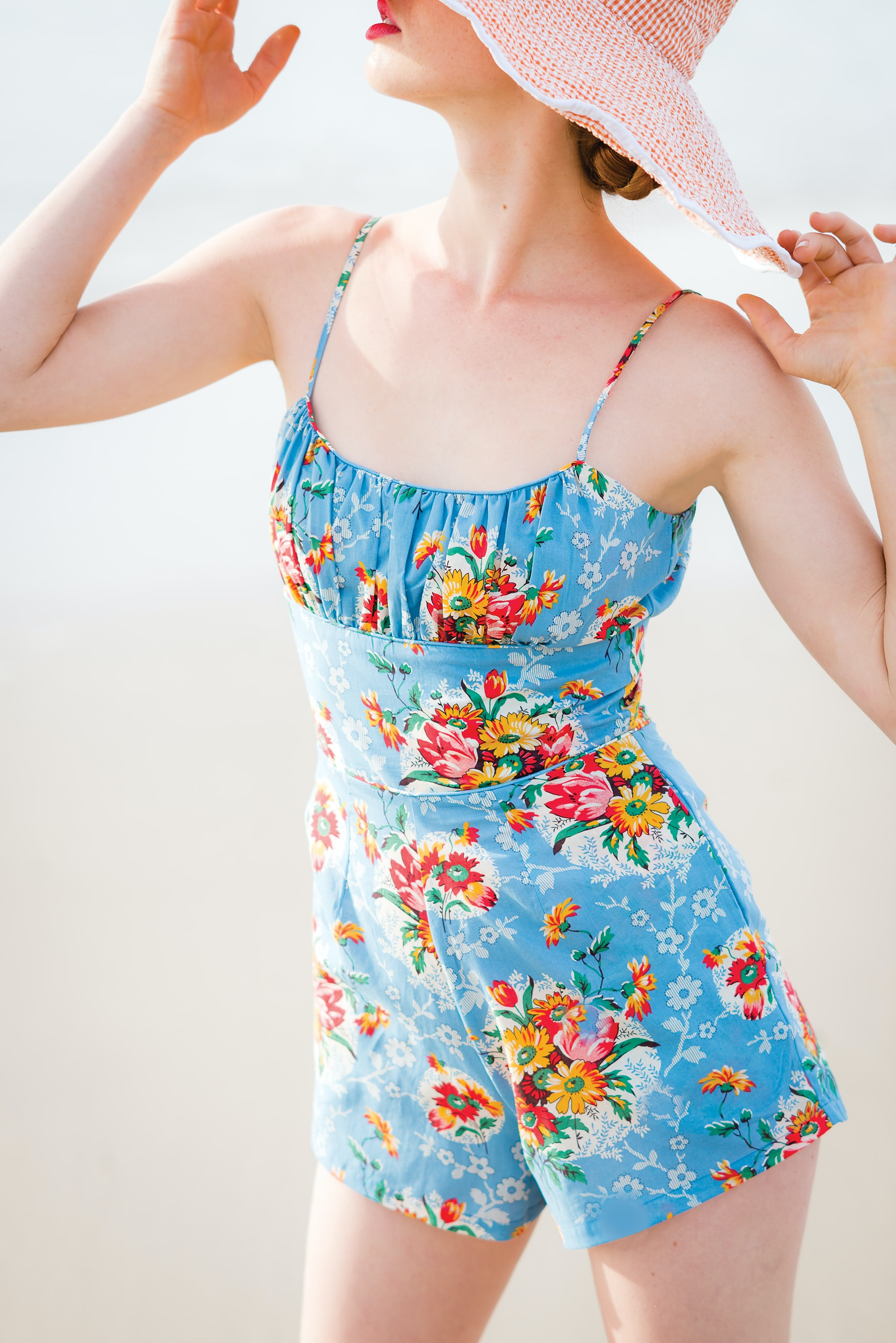 woman wearing blue floral rompers and brown hat