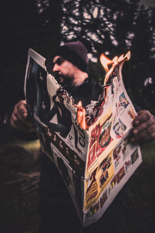 person holding firing newspaper