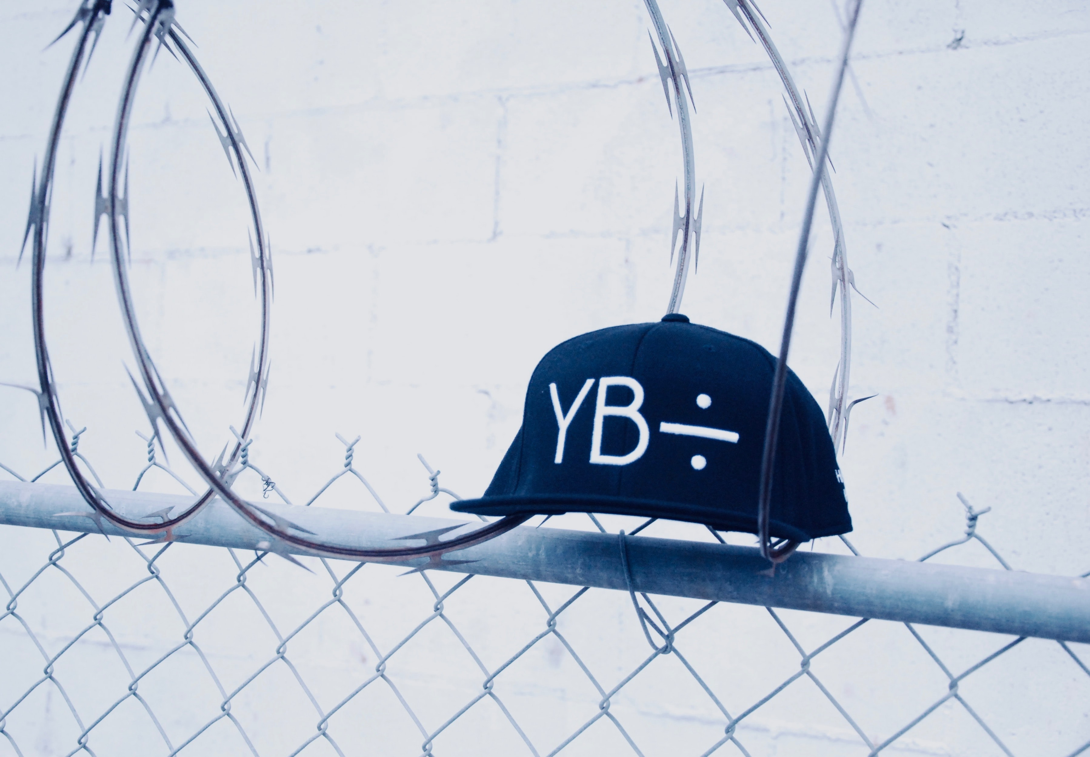 black YB fitted cap on gray cyclone fences