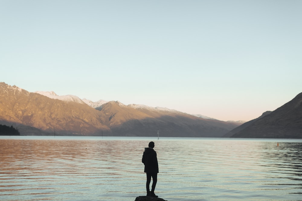 silhouette of person near calmly body of water over mountain under blue sky during daytime