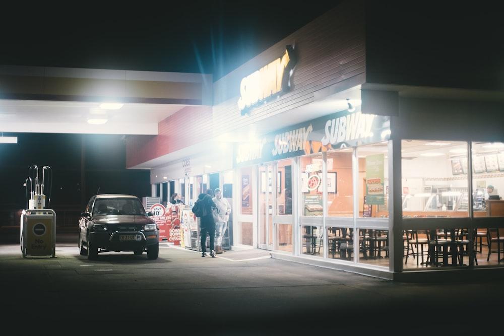 black car beside two men during night time
