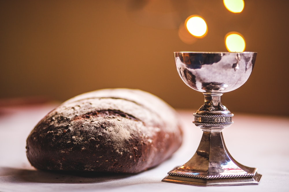 gray footed cup beside baguette bread