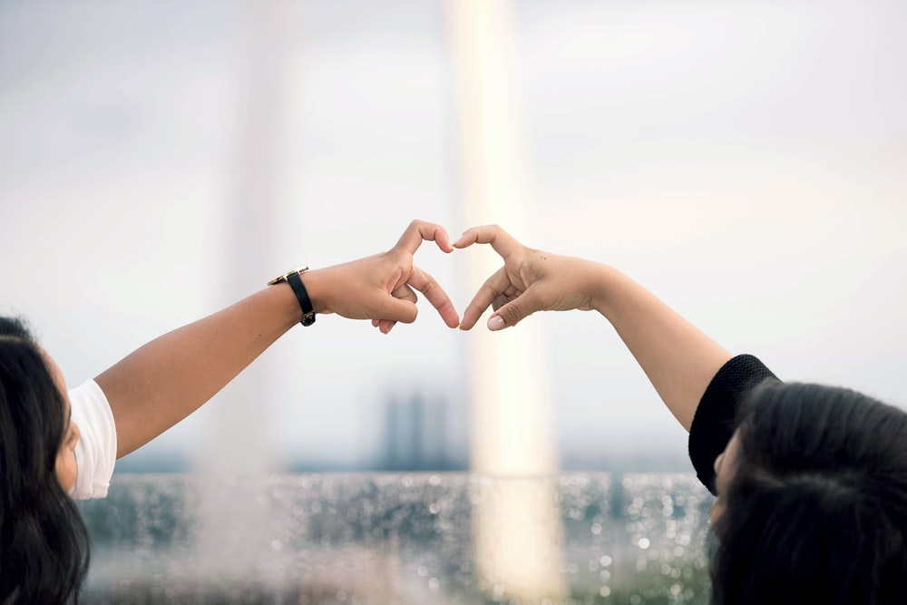 two person doing heart hand sign during daytime