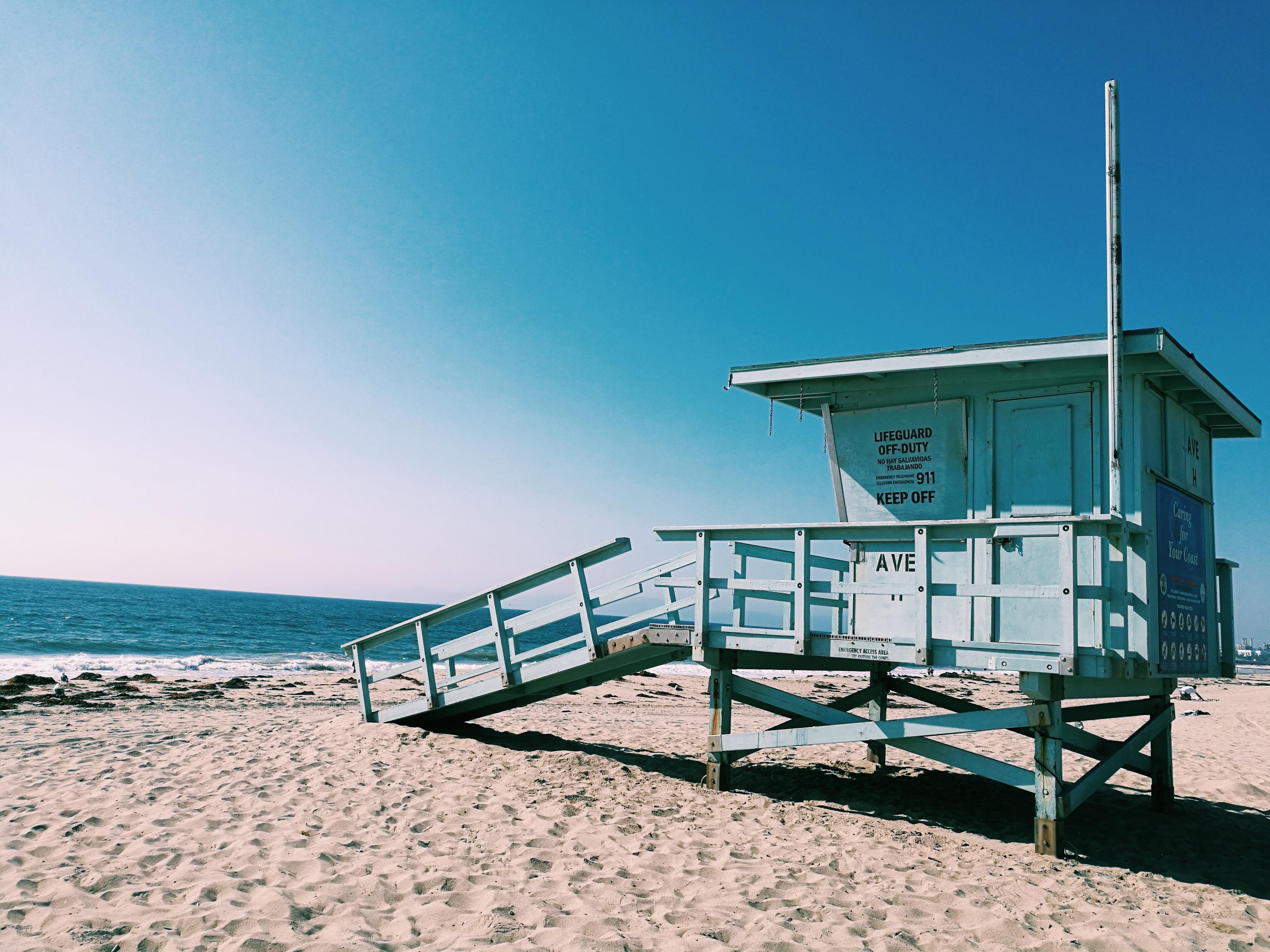 white wooden beach watch house near shore