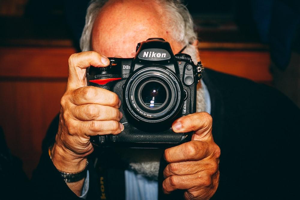 man holding black Nikon camera