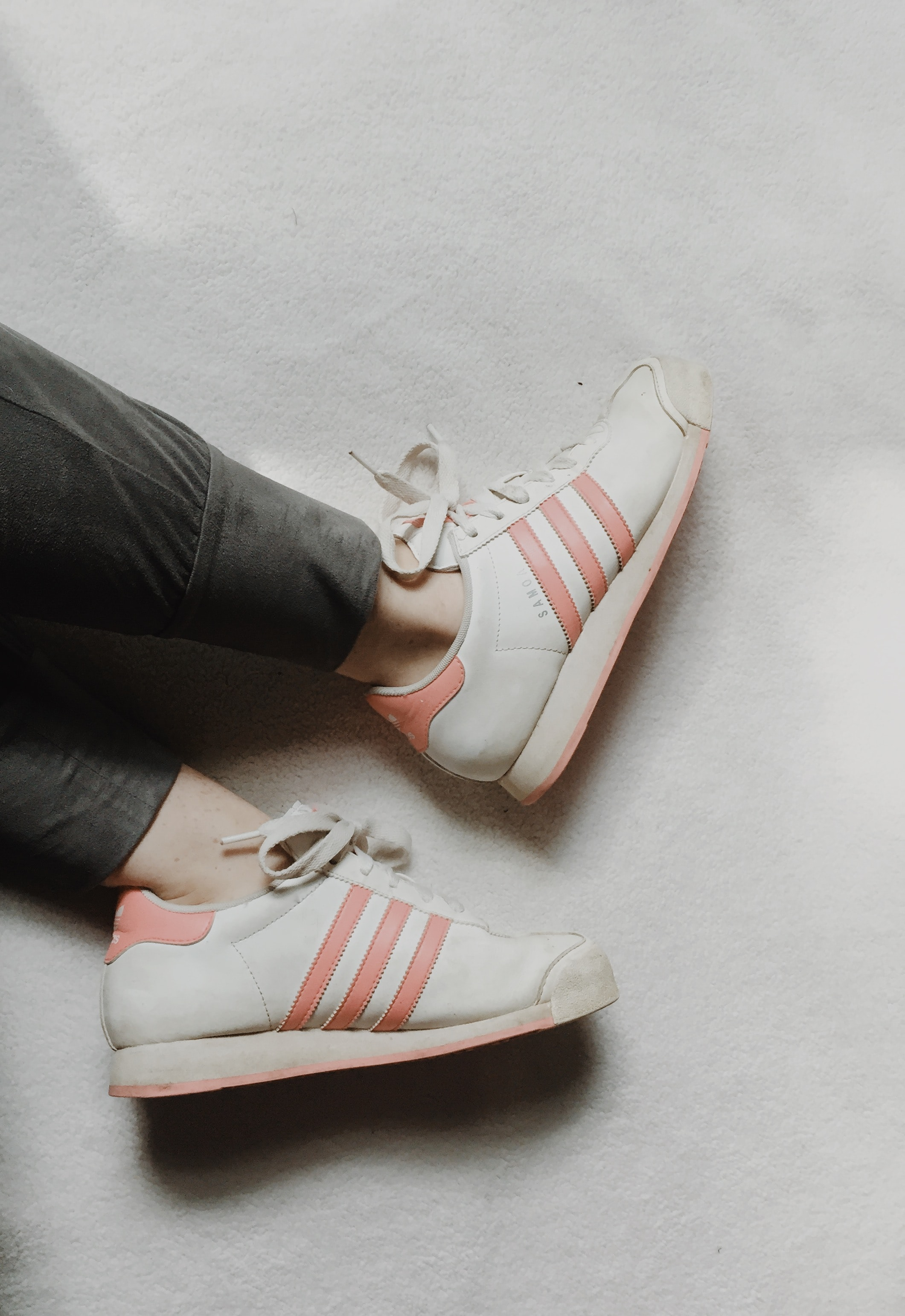person taking photo of white-and-red adidas low-top sneakers