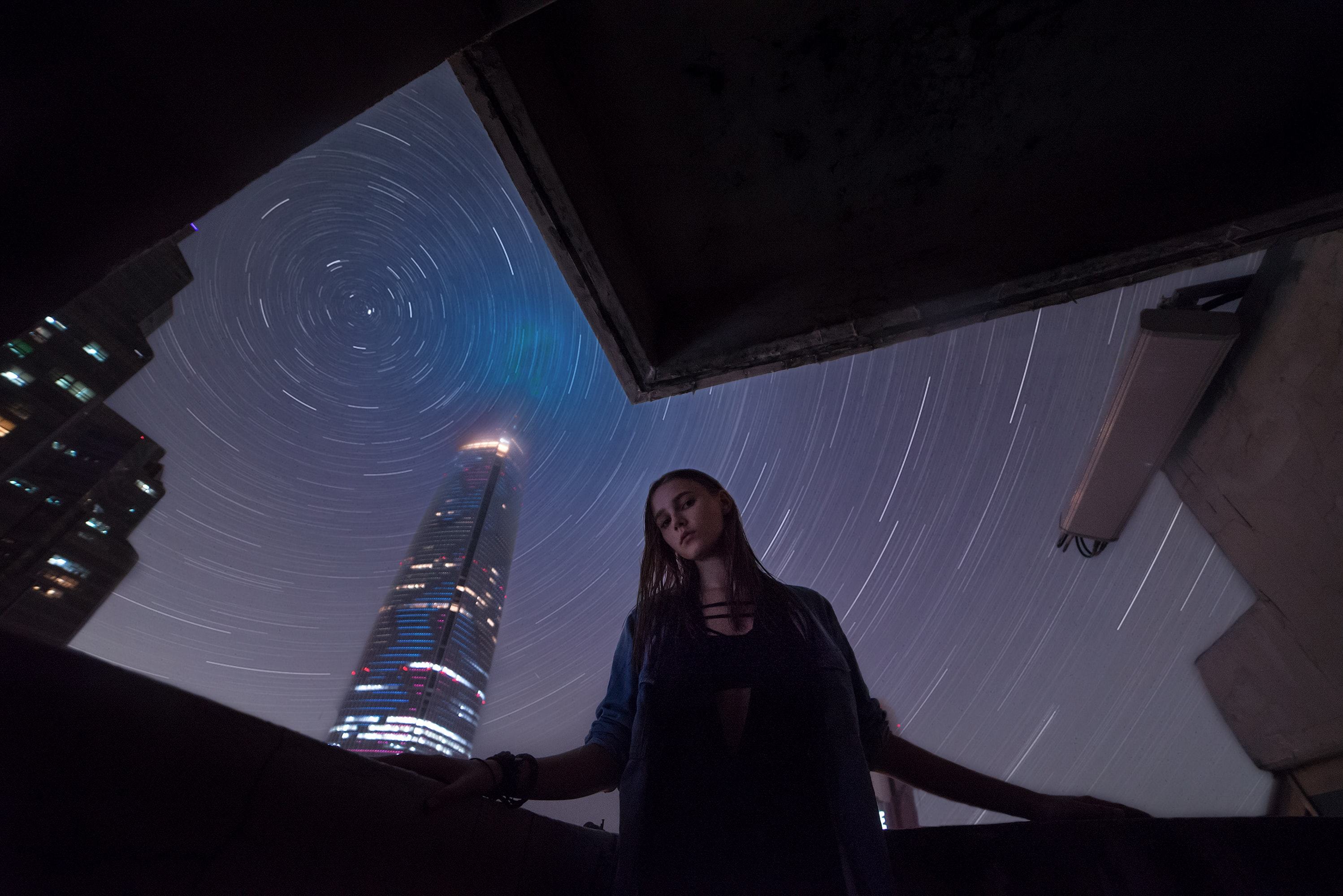 worm's-view photo of woman wearing jacket with time-lapse photo of star as background