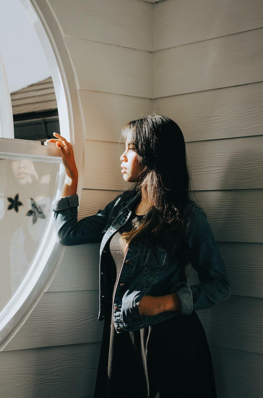 woman in blue denim jacket standing beside window