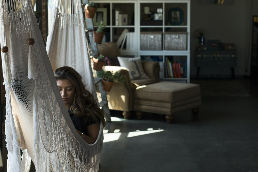 woman on white knit hammock during daytime