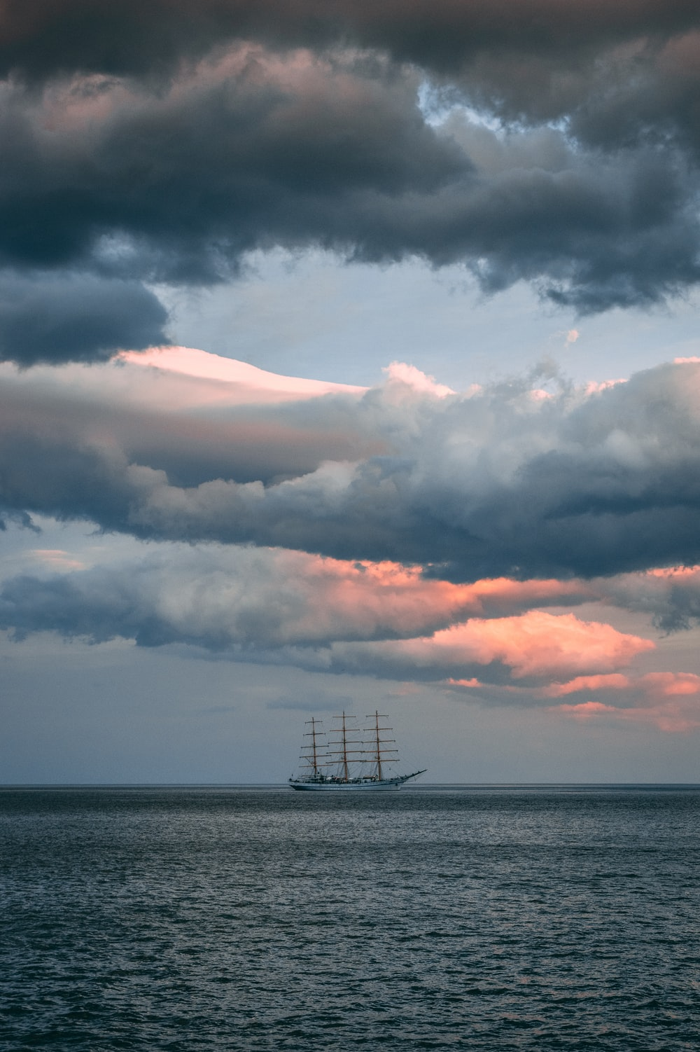 white and brown ship in ocean water under cloudy sky during daytime