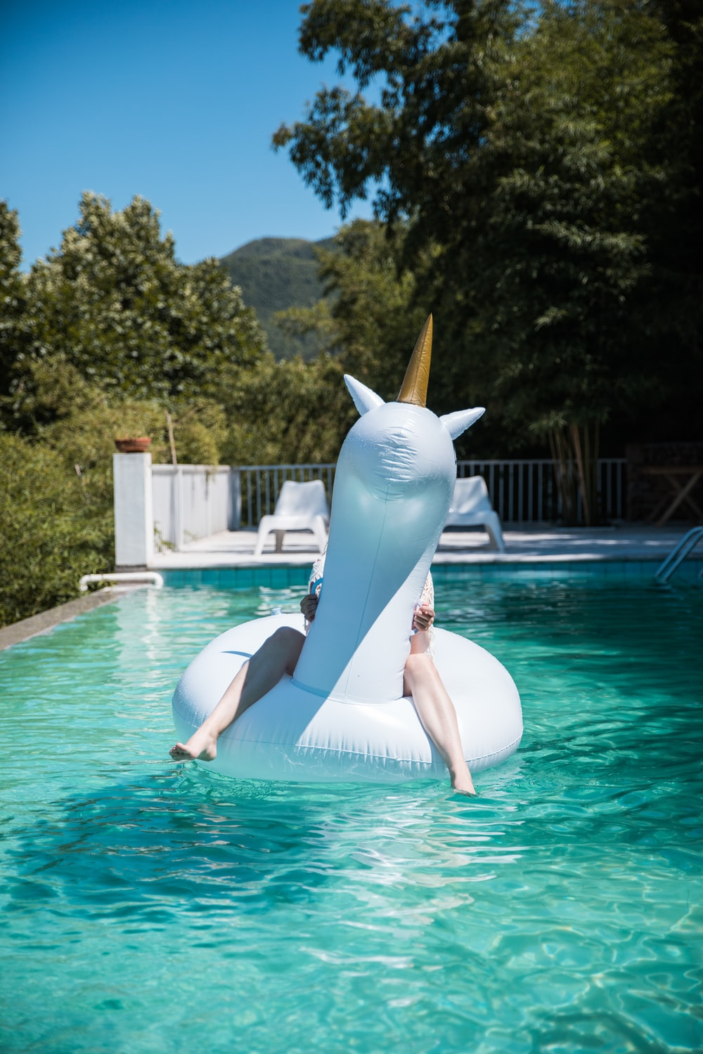 person riding unicorn inflatable ring on body of water