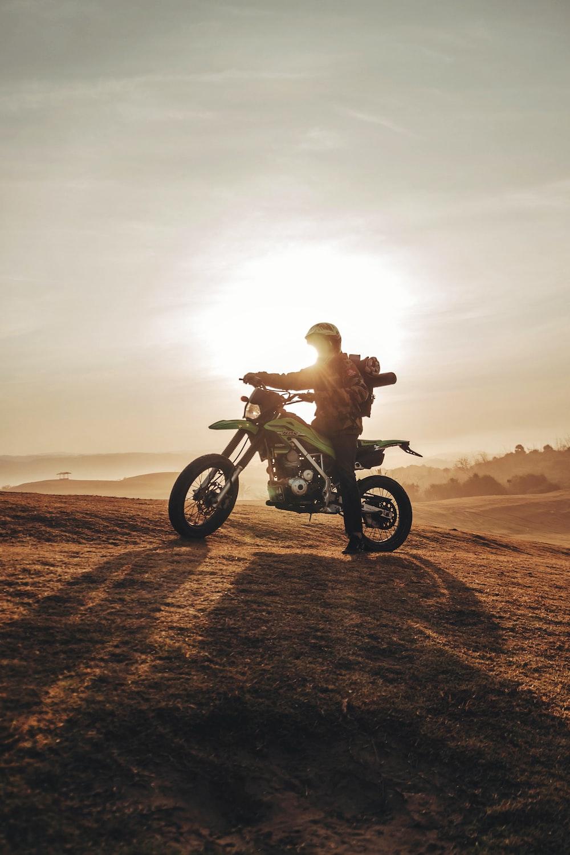 man riding green and black dirt bike on brown soil