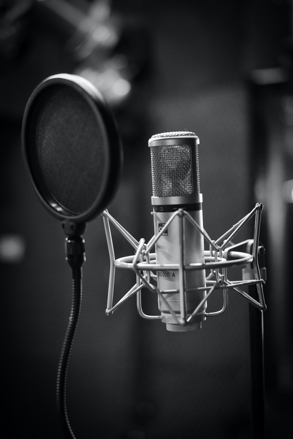 grayscale photo of condenser microphone beside pop filter