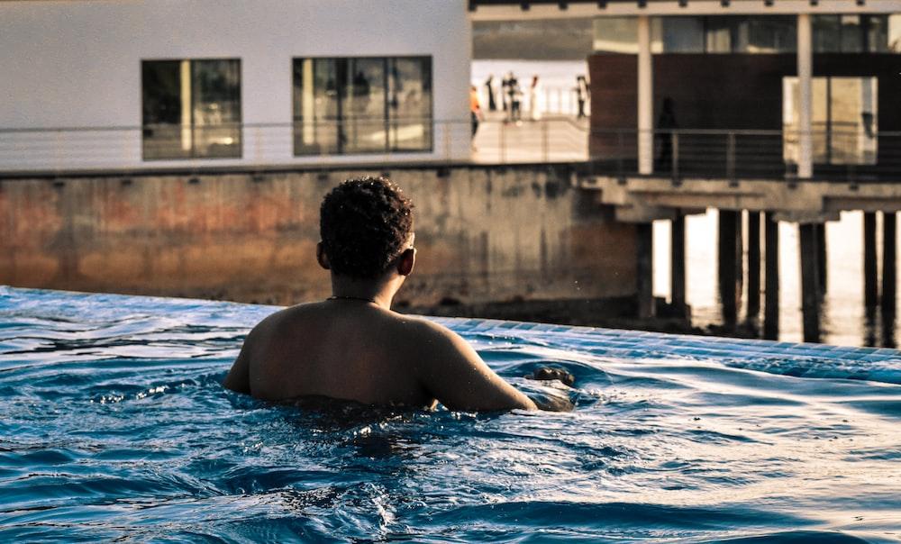 topless man swimming on pool
