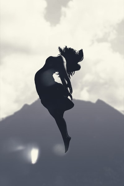 silhouette of person jumping in mid-air during daytime