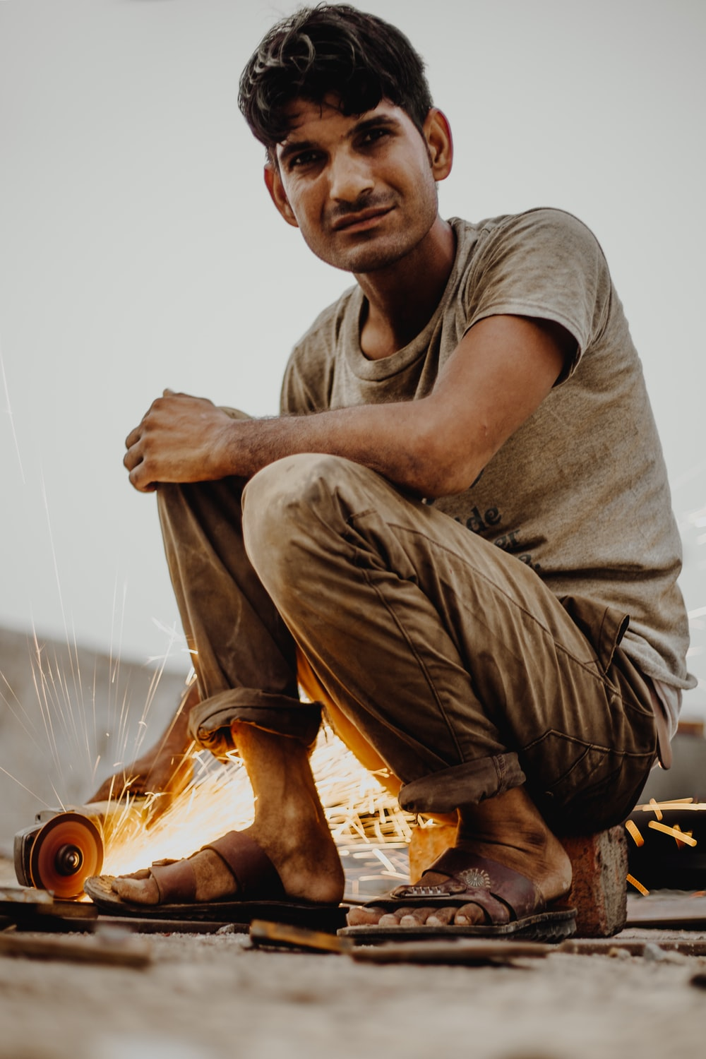 man sitting on gray stone holding angle grinder with sparks