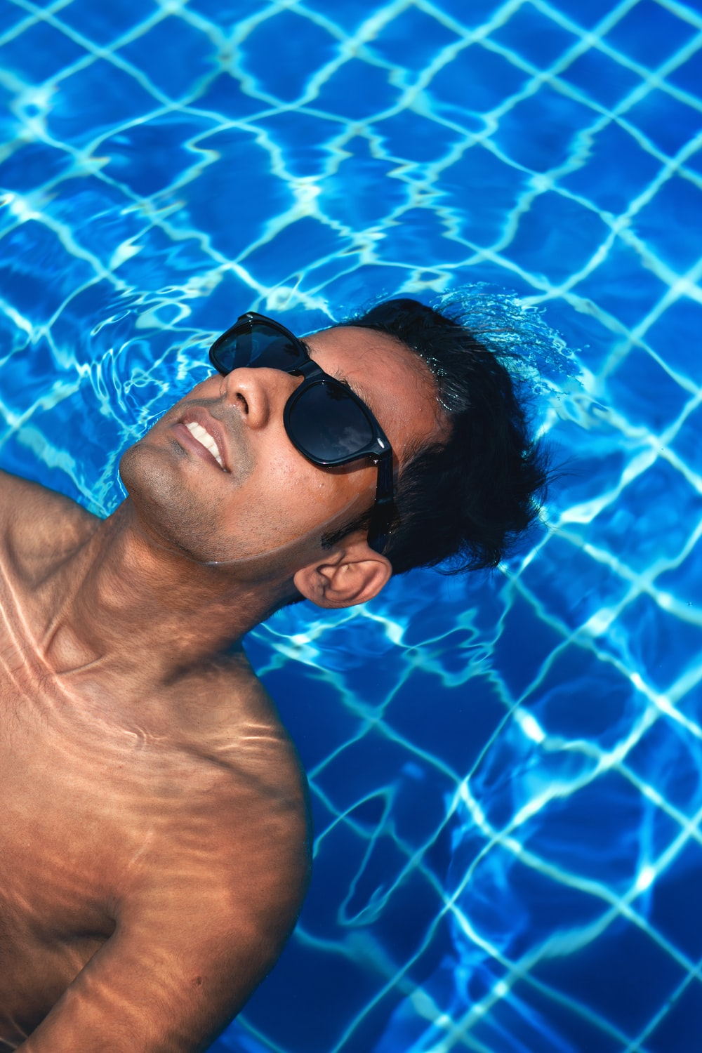 man wearing black framed sunglasses floating on body of water