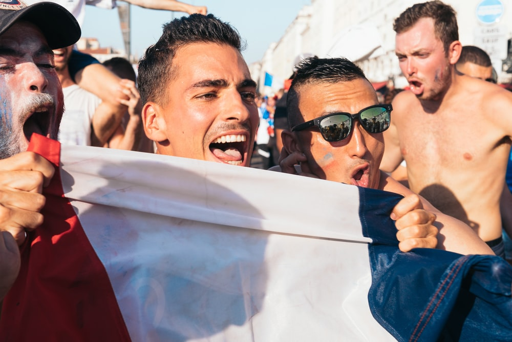 men holding flag near people during day