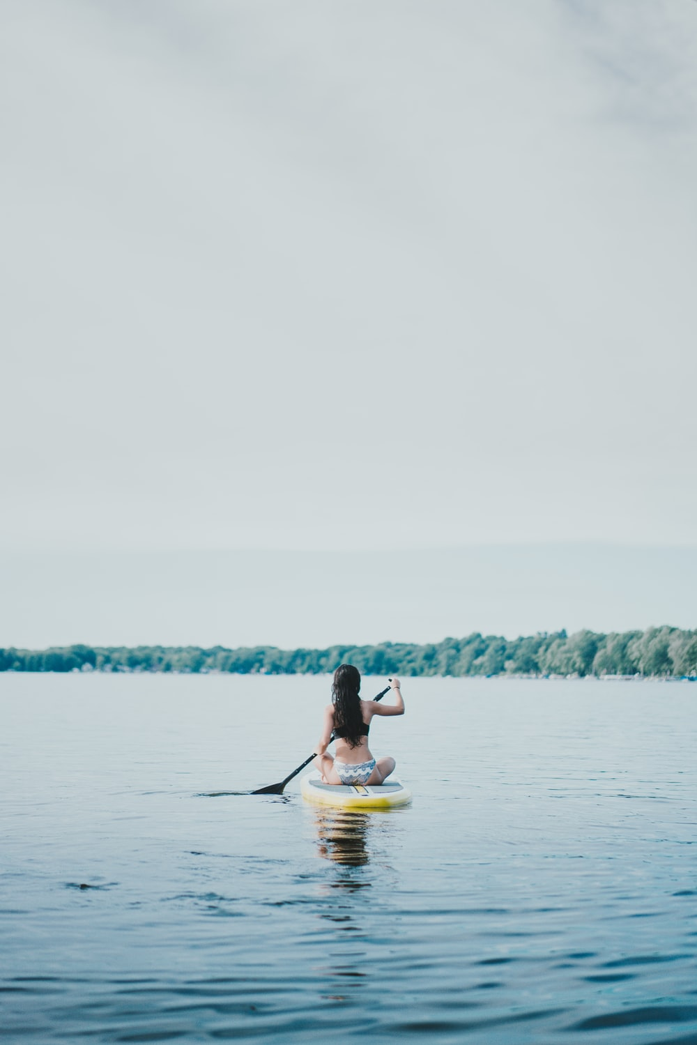 woman sitting on yellow paddle board during daytime