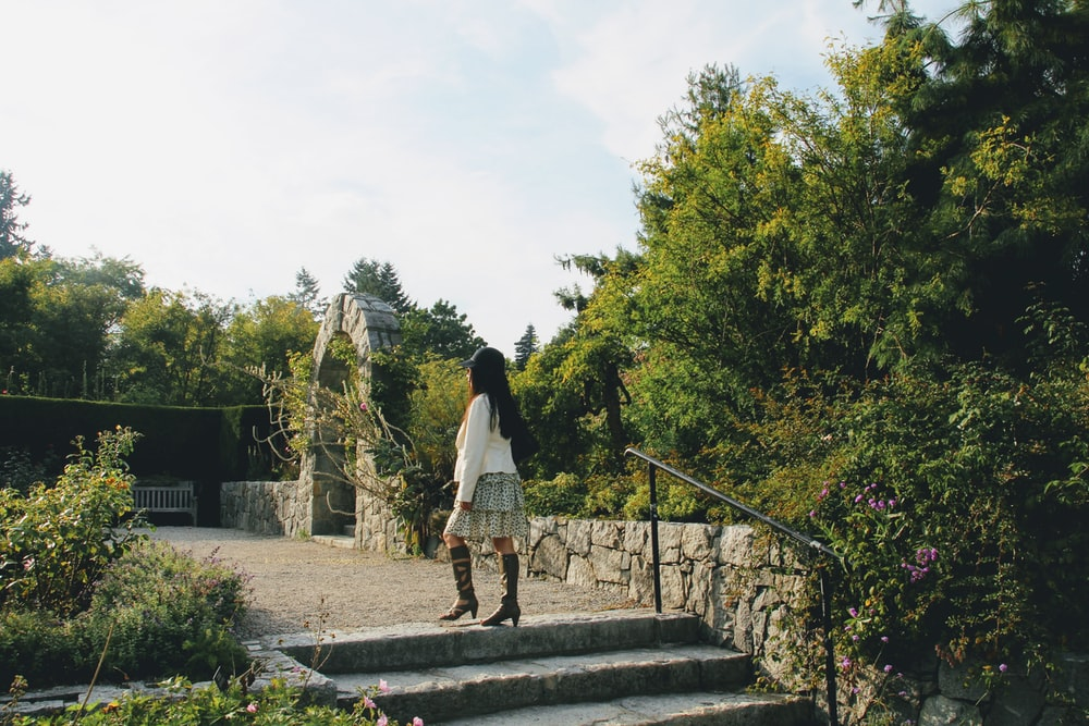 candid photography of woman standing at staircase outdoors
