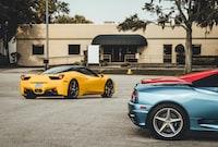 three Lamborghini coupes near building at daytime
