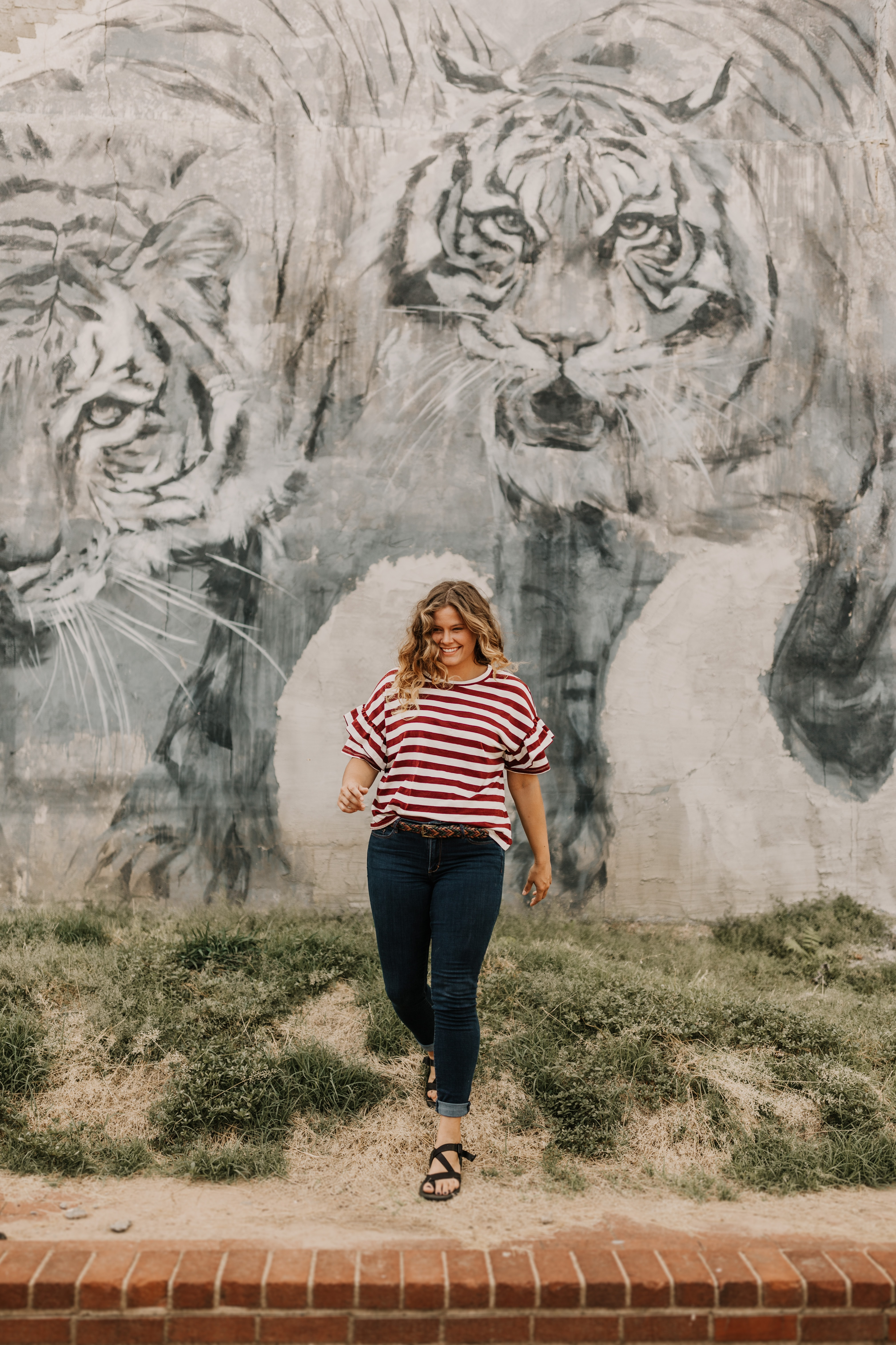 woman in standing beside tiger-printed wall