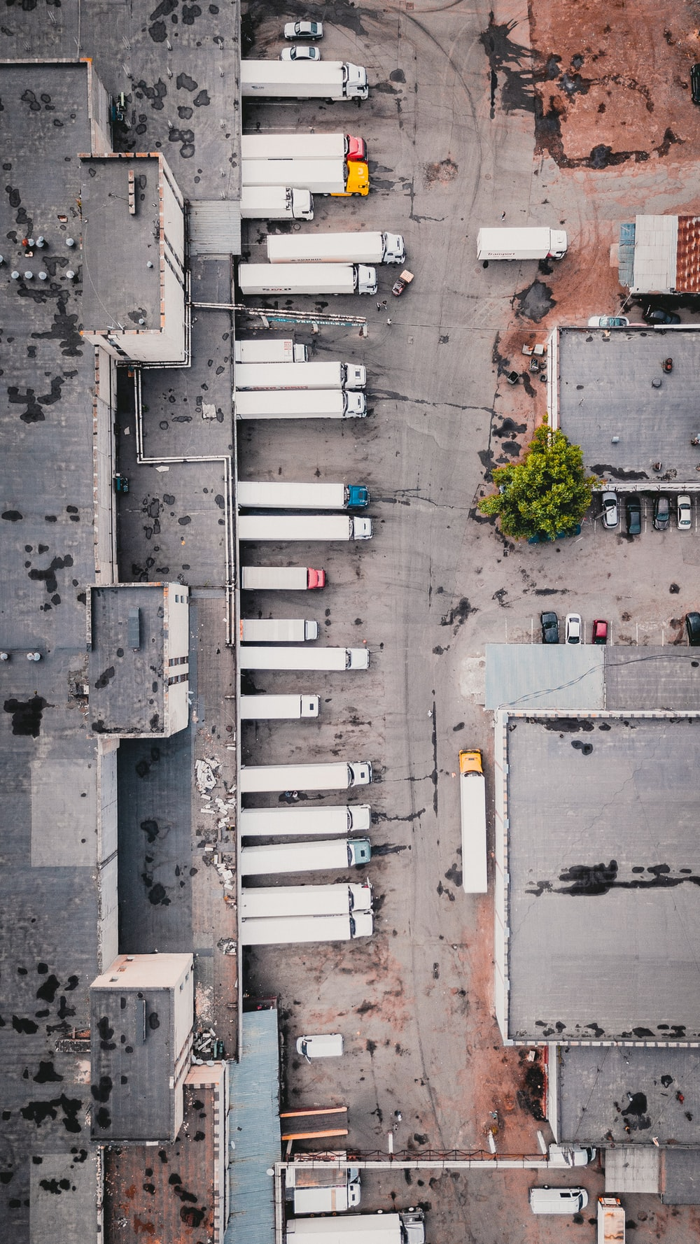 aerial view of trucks on gray commercial building during daytime