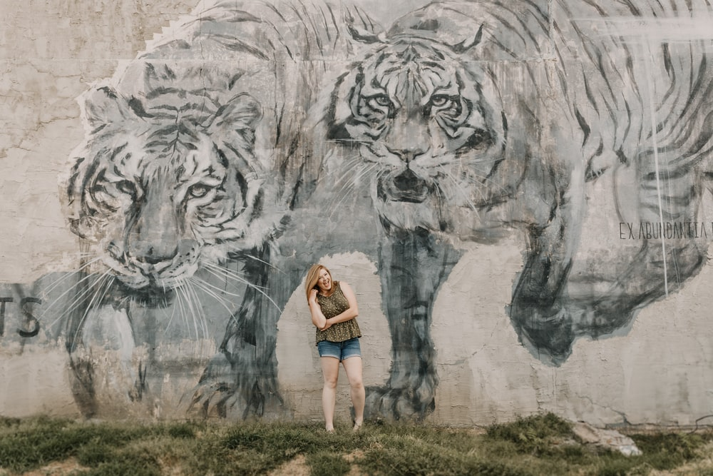 woman and gray sleeveless shirt beside tiger graffiti