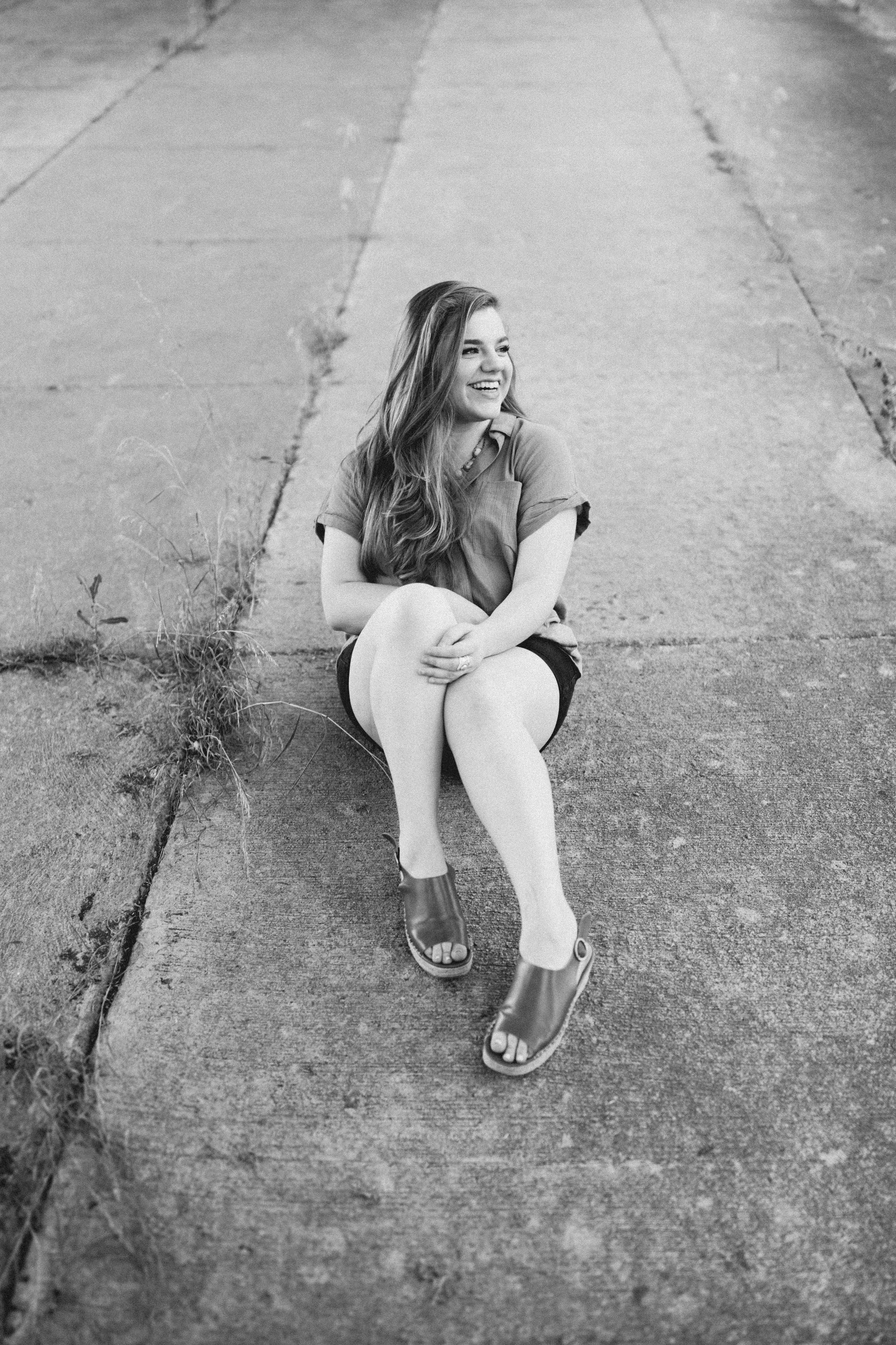 grayscale photo of sitting woman