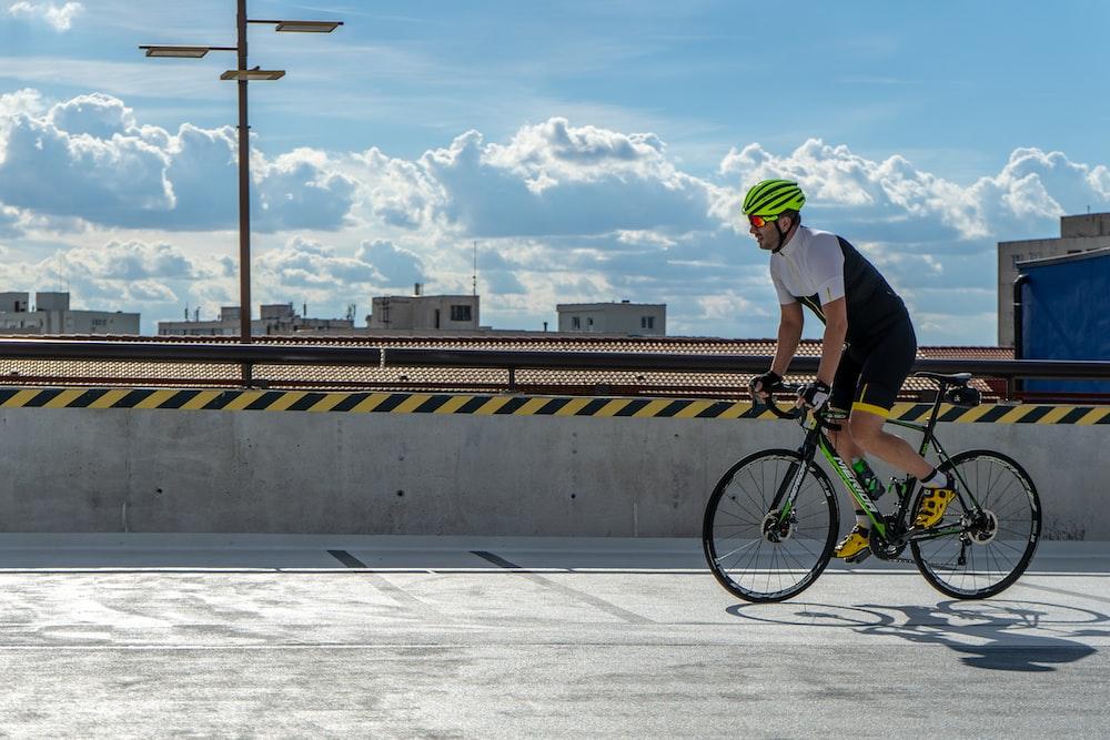 man riding on road bike