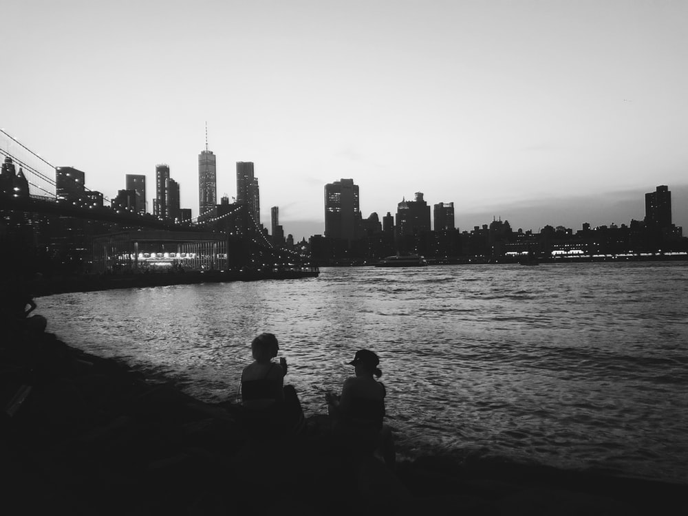 grayscale photo of two women sitting and facing sea