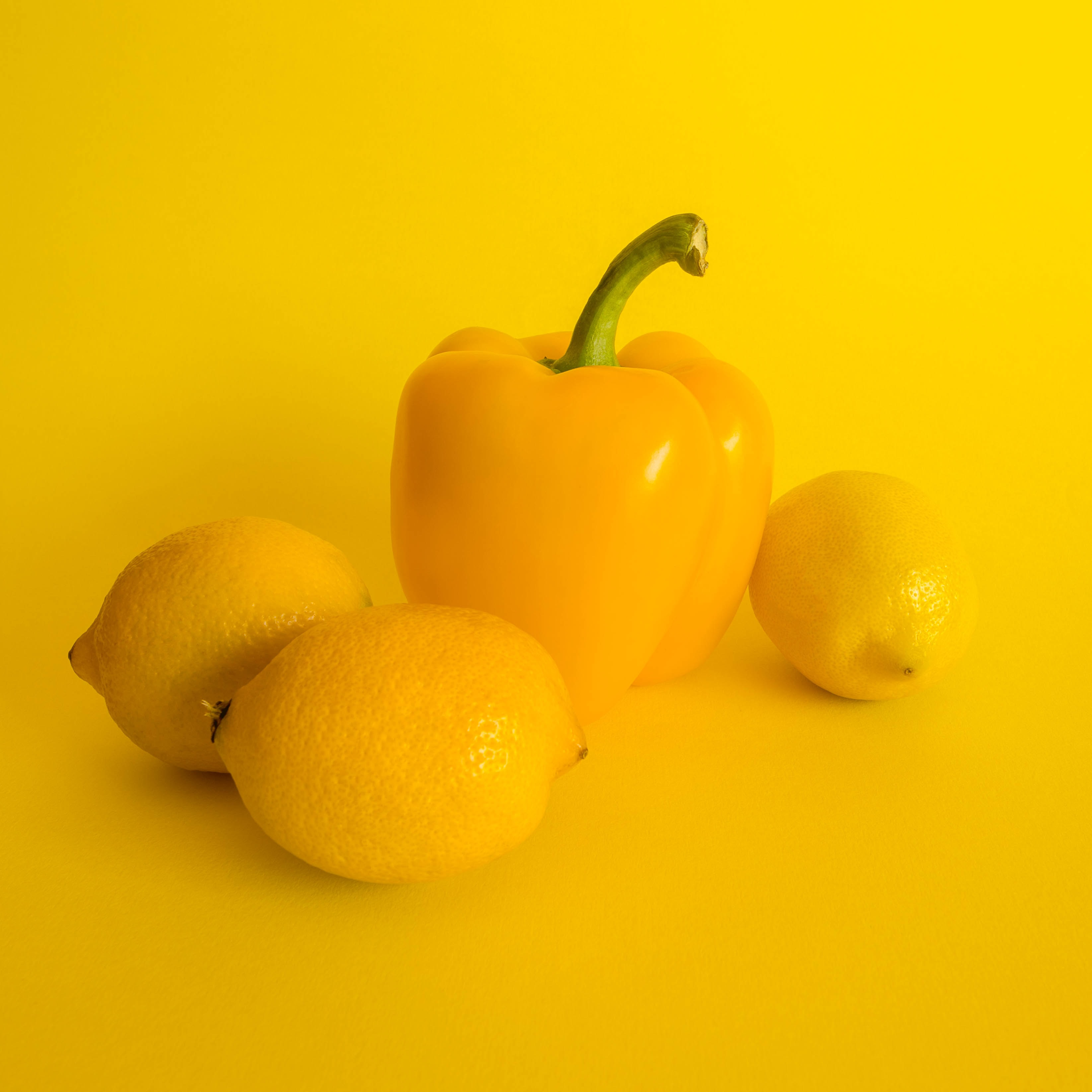 three lemons and yellow bell pepper