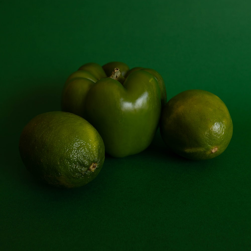 chili pepper and green fruit on green surface