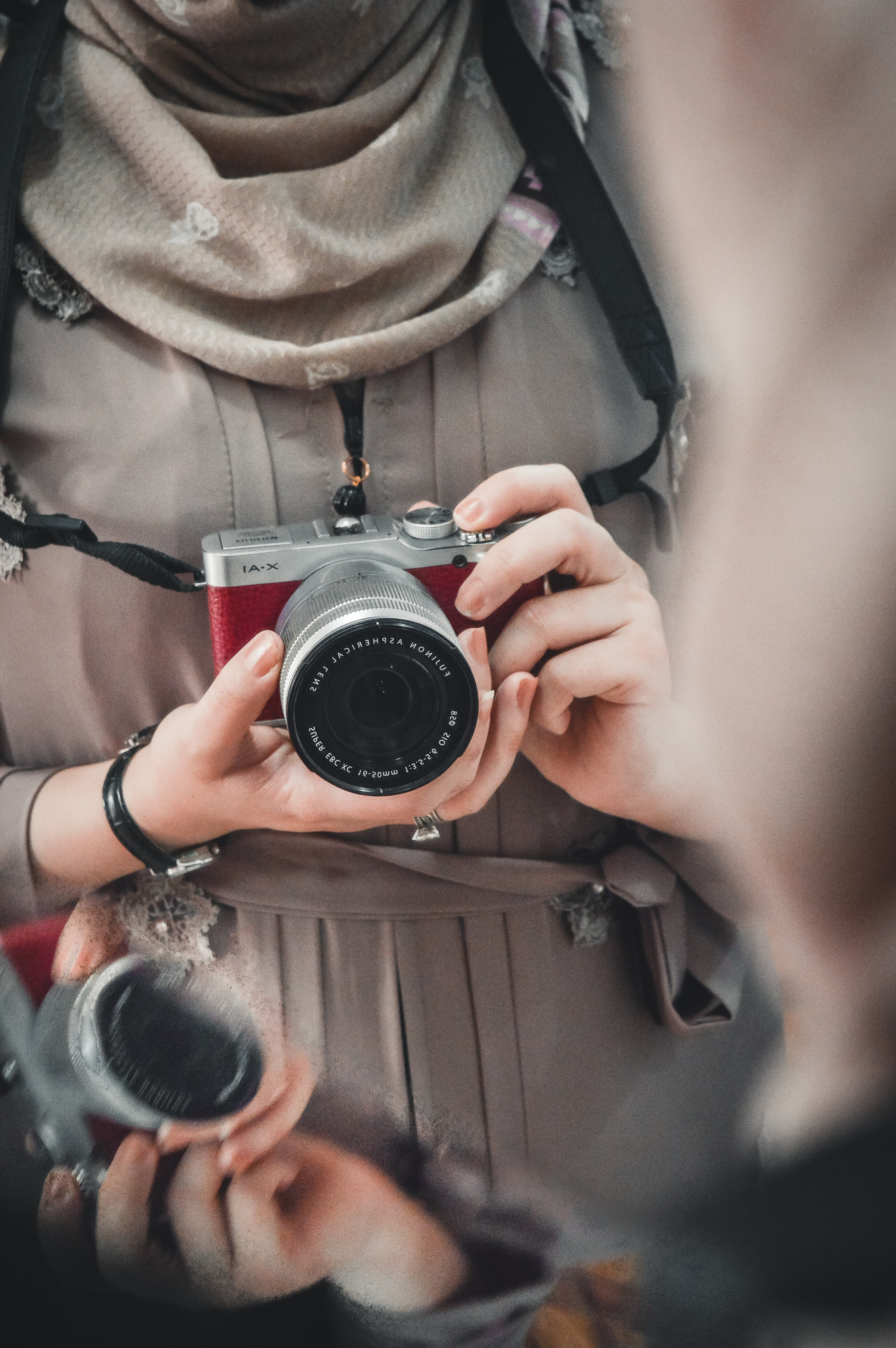 person holding red and silver SLR camera