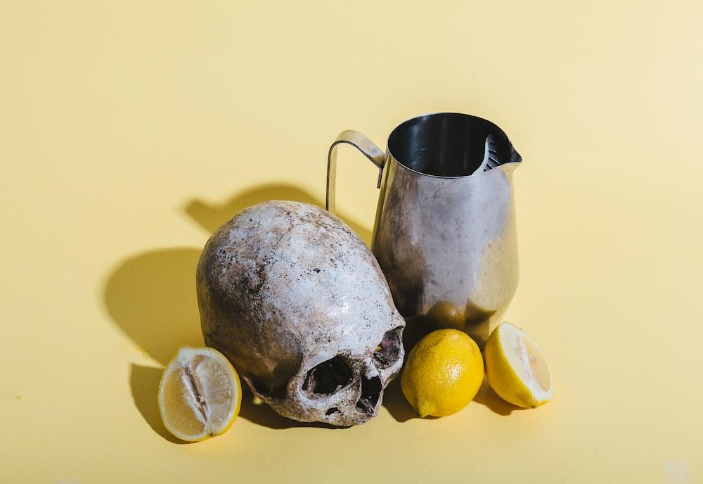 human skull beside pitcher and lemons