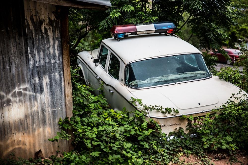 white police car near a black house