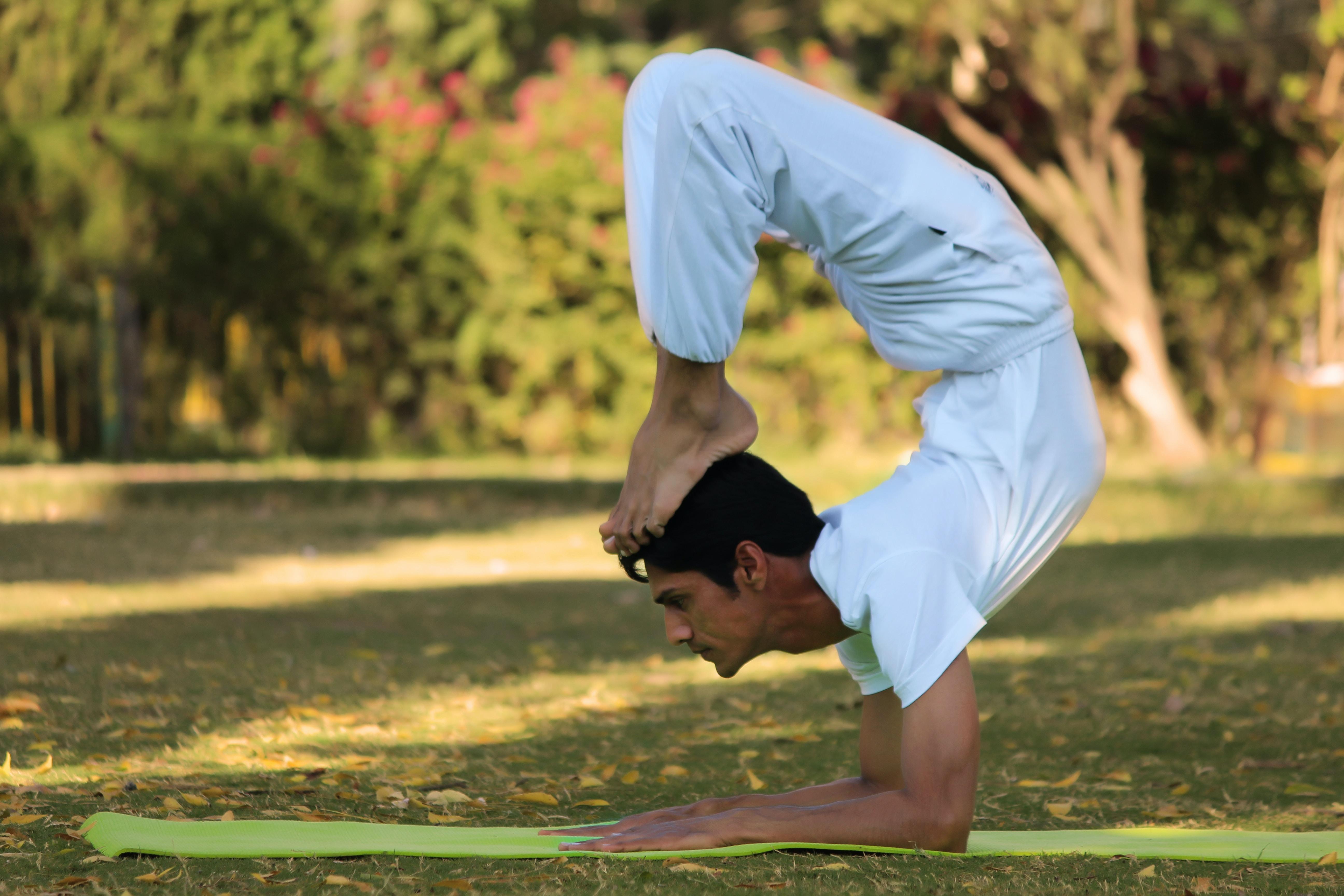 man acrobating on green pad during daytime