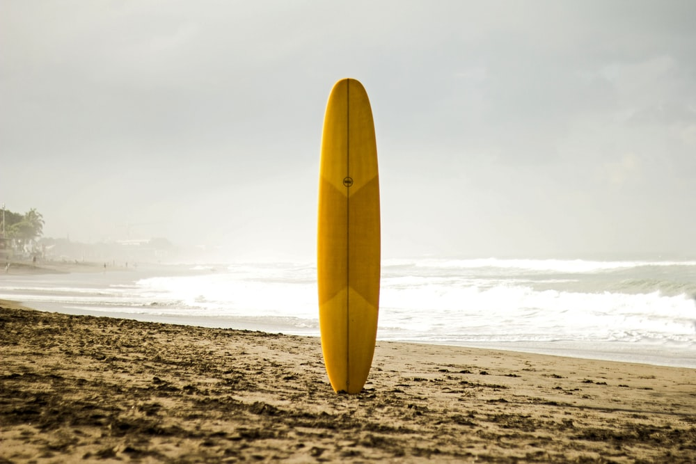 brown surfboard standing on sea shore