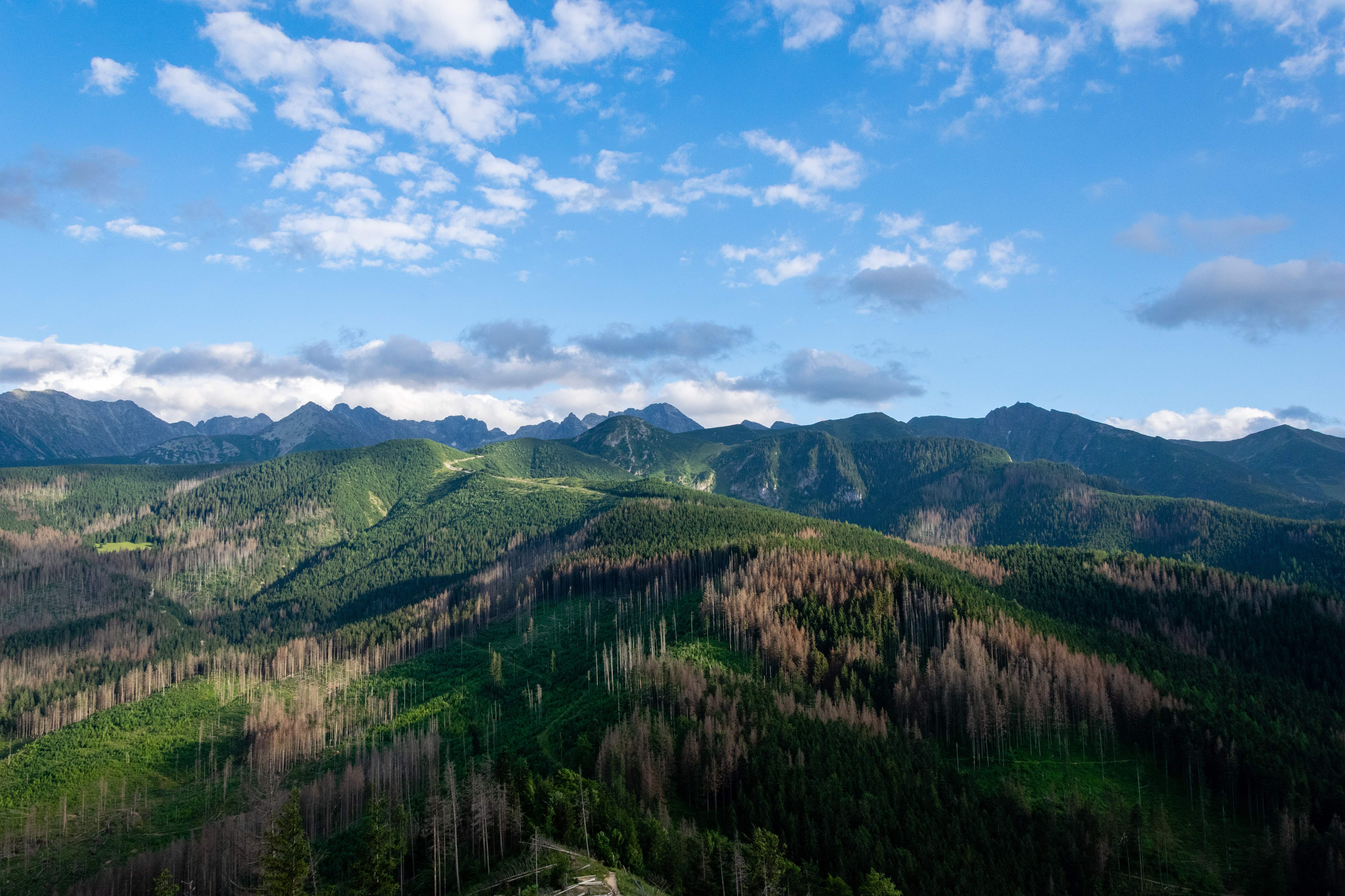 bird's-eye photography of mountains under cirrus clouds and blue calm sky