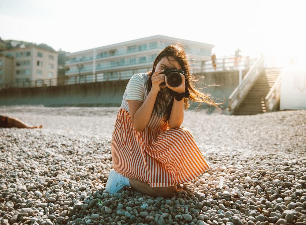 woman holding camera taking photo