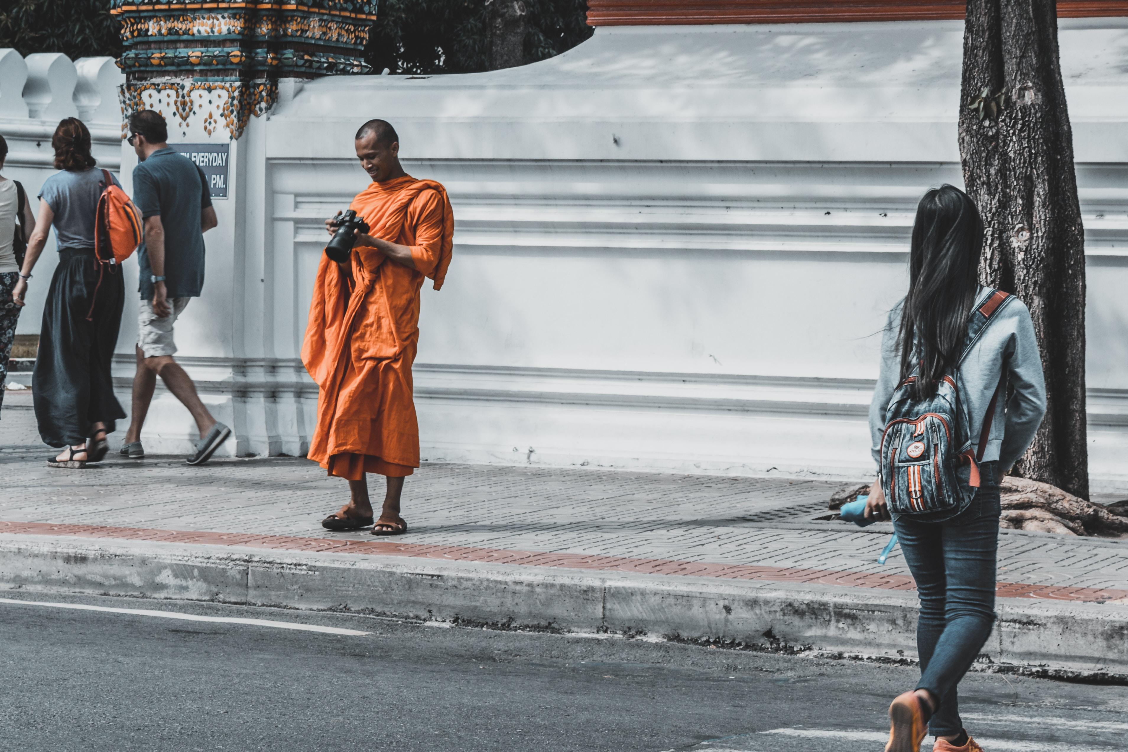 monk holding black DSLR camera while smiling