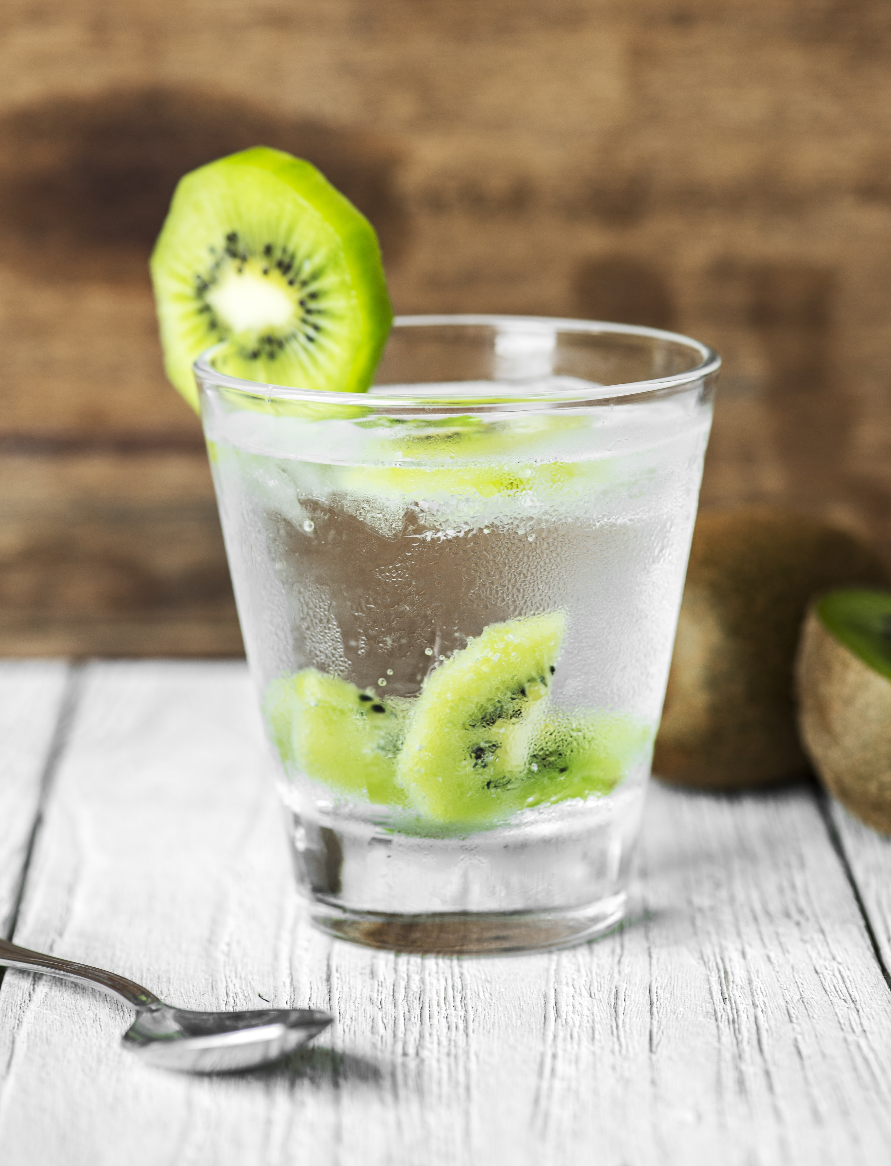 water in glass with sliced kiwi