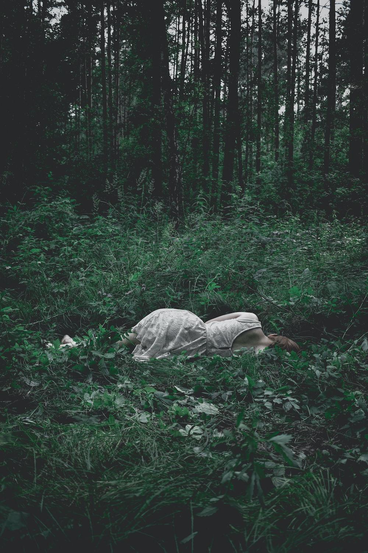 woman lying on green plants
